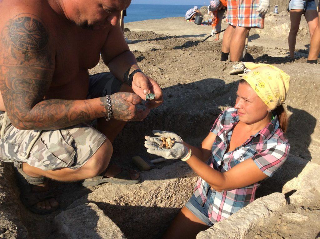 Руководитель экспедиции археолог Павел Гецко рассматривает найденные предметы